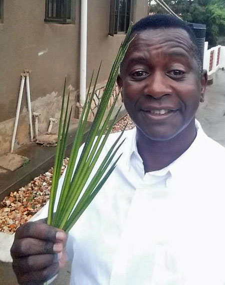 The Rev. Anthony Musaala offers palm fronds. (Photo courtesy of Facebook)